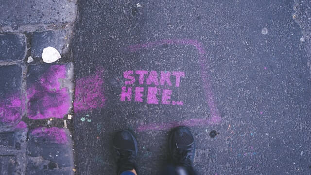 'Start Here' graffiti on road, in front of two feet.