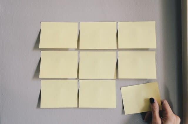 Nine blank post-its attached to a wall, with a hand placing the ninth.